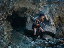 Cavewoman hunting with spear. Caucasian woman dressed as a caveman holding a spear, getting ready for hunting, close to a rocky cave Stock Image
