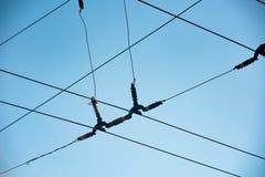Cavi d'intersezione con l'isolante di sezione contro un cielo blu fotografia stock