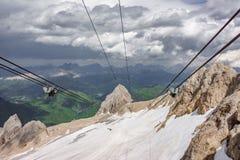 Cavi e ruote della cabina di funivia contro roccia verticale, picco di Marmolada Fotografia Stock