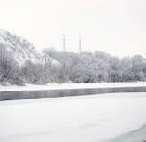 Cavi elettrici ad alta tensione della colonna sulle banche del fiume i Immagine Stock