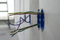 Cavi elettrici che attaccano da una parete immagine stock