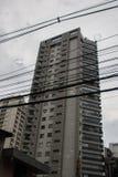 Cavi elettrici che passano davanti ad un edificio alto residenziale Immagini Stock