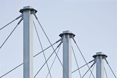 Cavi legati del tetto della sospensione, tre Grey Masts alto, ancore Swooping Cavo-sospese del pilone del tetto, Pale Blue Summer Immagine Stock