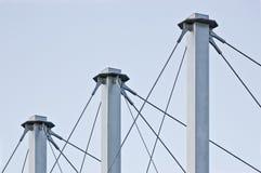 Cavi legati del tetto della sospensione, tre Grey Masts alto, ancore Swooping Cavo-sospese del pilone del tetto, Pale Blue Summer Fotografia Stock