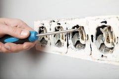 Cavi nocivi in sbocco elettrico in parete Violazione delle regole elettriche di sicurezza immagine stock libera da diritti