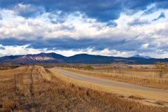 Cavi rurali della strada verso una zona distante di indicatore luminoso Immagini Stock Libere da Diritti