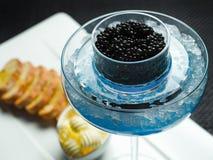 Caviale nero sul piatto bianco, in vetro blu Fotografie Stock