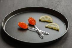 Caviale rosso in cucchiaio e limone Immagine Stock