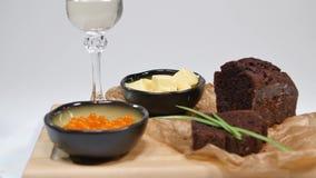 Caviale rosso fresco con basilico e burro su pane in studio Cresciuto con il caviale rosso con i vetri di vino su fondo freddo archivi video