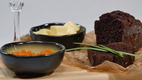 Caviale rosso fresco con basilico e burro su pane in studio Cresciuto con il caviale rosso con i vetri di vino su fondo freddo video d archivio