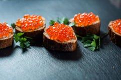 Caviale rosso sul fondo dell'ardesia Fotografia Stock
