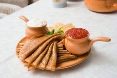 Caviar. Russian pancakes with caviar and sour cream stock photos