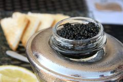 Caviar. Black caviar on top of ice with lemon and toast in background Stock Photography