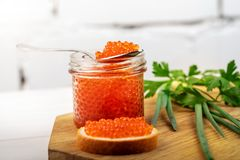 caviar appetizer - jar with red roe and herbs on the table stock image