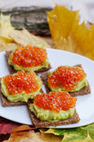 Caviar And Avocado Appetizer. Grain bread with avocado paste and red caviar Royalty Free Stock Images