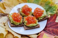 Caviar And Avocado Appetizer. Grain bread with avocado paste and red caviar Royalty Free Stock Photos