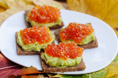 Caviar And Avocado Appetizer. Grain bread with avocado paste and red caviar Stock Photography