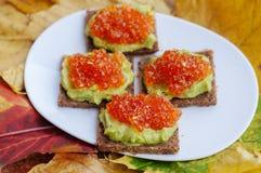 Caviar And Avocado Appetizer. Grain bread with avocado paste and red caviar Stock Photos