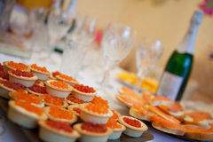 Caviar and champagne. Sandwiches with red caviar, glasses of champagne on a table Stock Photo