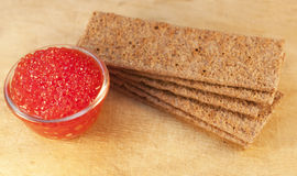 Caviar and crisps on wooden background Royalty Free Stock Photography