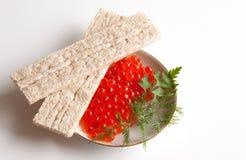 Caviar de um salmão em um saucer e em uns loafs pequenos Foto de Stock