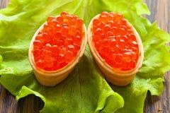 Caviar dos, dispersado en cabezas de un hueso cocidas de la galleta en la ensalada verde de la hoja Fotos de archivo