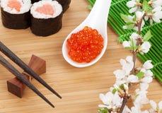 Caviar, grupo do sushi, ramo de sakura e hashis vermelhos Imagem de Stock Royalty Free