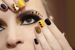 Caviar manicure and makeup. Caviar manicure in yellow and black nail Polish on the girl with false eyelashes and rhinestones of different shapes Stock Images