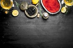 Caviar negro y rojo con las rebanadas del limón Foto de archivo