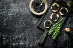 Caviar noir sur des tranches de pain avec l'aneth images libres de droits