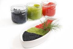 CAVIAR IN THE OPEN GLASS CONTAINERS. Caviar in a bowl-shaped over on withe background stock photography