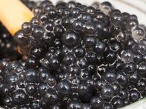 Caviar preto do alabote com a colher no frasco de vidro Imagem de Stock Royalty Free