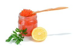 Caviar red in a glass jar with lemon and parsley Stock Photo