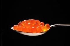 Caviar rojo contra fondo negro Imagen de archivo