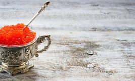Caviar rojo de color salmón en el cuenco de plata Foto de archivo libre de regalías