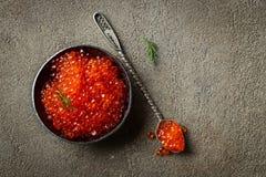Caviar rojo delicioso en cuenco negro en un fondo concreto oscuro Visi?n superior con el espacio de la copia Endecha plana foto de archivo libre de regalías