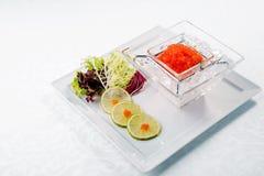 Caviar rojo en cierre del hielo para arriba con la cal Alimento de mar De madera Foto de archivo libre de regalías