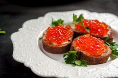 Caviar rojo en el pan negro con mantequilla Alimento sano Aperitivo de los pescados Fondo oscuro fotos de archivo libres de regalías