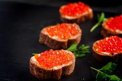 Caviar rojo en el pan negro con mantequilla Alimento sano Aperitivo de los pescados Fondo oscuro fotos de archivo