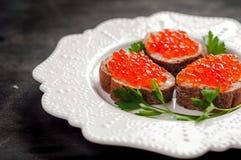 Caviar rojo en el pan negro con mantequilla Alimento sano Aperitivo de los pescados Fondo oscuro foto de archivo