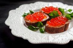 Caviar rojo en el pan negro con mantequilla Alimento sano Aperitivo de los pescados Fondo oscuro imagenes de archivo