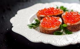 Caviar rojo en el pan negro con mantequilla Alimento sano Aperitivo de los pescados Fondo oscuro foto de archivo libre de regalías