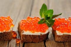 Caviar rojo en el pan y la mantequilla de centeno con la menta fresca Foto de archivo