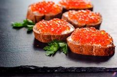 Caviar rojo en fondo de la pizarra imagenes de archivo