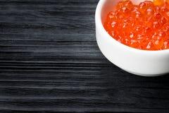 Caviar rojo en una taza con la sal en la tabla de madera imagen de archivo