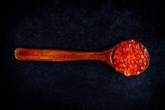 Caviar rojo fresco en una cuchara de madera Foto de archivo libre de regalías