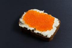 Caviar rojo y mantequilla manchados en un pedazo de pan negro Fotografía de archivo