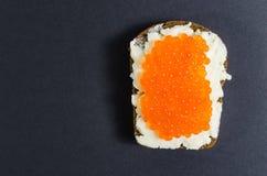 Caviar rojo y mantequilla manchados en un pedazo de pan negro Foto de archivo libre de regalías