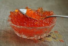 Caviar rouge dans un bol en verre et une cuillère dans elle Photo libre de droits