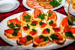 Caviar rouge dessus multiplié du plat blanc photos stock
